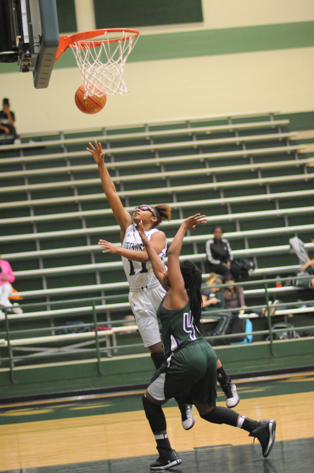 Jhonrekia Ramsey-Dunn (11) of Livingston scores two of her game high 23 points against Bryan Rudder in District 18-5A basketball action at Lion gym.