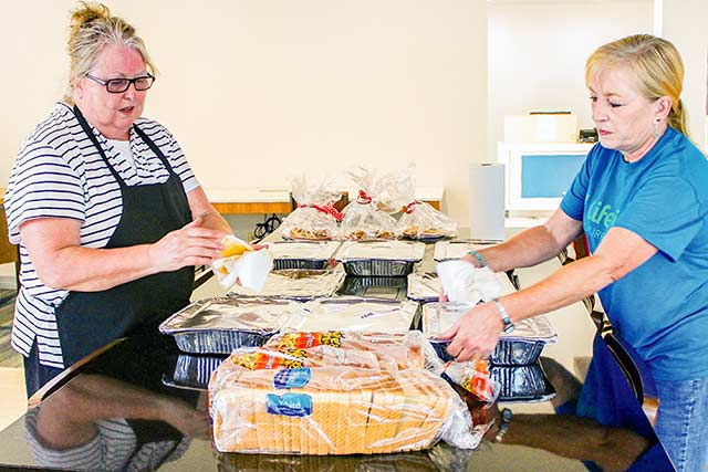 FOOD FOR EVACUEES -- Local church volunteers delivered free homemade dinners and dessert for flood evacuees affected by Hurricane Harvey staying at motels in Livingston last week. Pictured are Beverly Cadwell and Juana Leigh Baker of Life Vine Church serving trays full of barbecue at the Holiday Inn Express. Many of the motel guests include Polk County residents forced from their homes by local flooding. (ENTERPRISE PHOTO BY ALBERT TREVINO)
