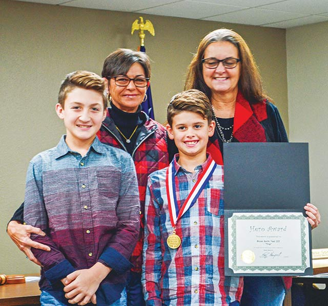 "HERO AWARD -- Brian ""Trip"" Keith Teel III, 9, (front right) was presented with a Hero Certificate and medal during last week's Onalaska City Council meeting. He is pictured with his older brother, mother and Aunt Kathy."