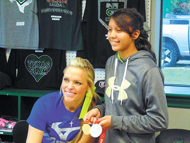 OLYMPIC CHAMPION — Softball legend Jennie Finch (left) shows her Olympic gold and silver medals to a young softball student during her visit to Livingston Saturday. Finch provided softball instruction to over 100 students at the Texas Slam Academy (ENTERPRISE PHOTO BY BRIAN BESCH)